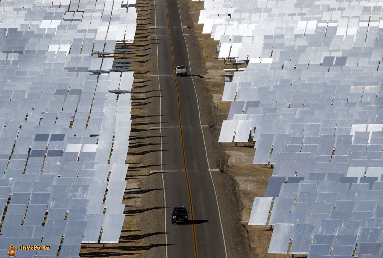 Vehicles drive through field of heliostats at the Ivanpah Solar Electric Generating System in the Mojave Desert near the California-Nevada border