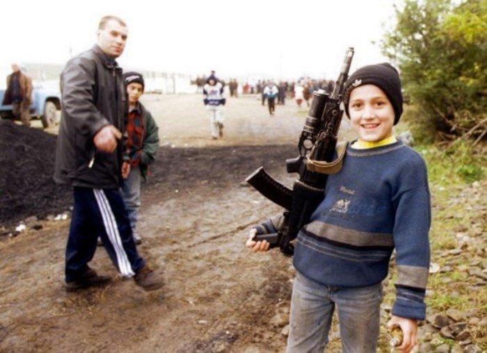 Чеченский мальчик с автоматом в лагере для беженцев. Ингушетия, ноябрь 1999 года.
